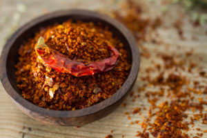 Wooden bowl full of fiery chilli pepper flakes.